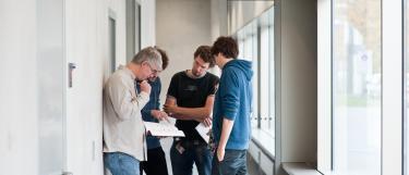 Dozent im Gespräch mit Nachwuchswissenschaftlern