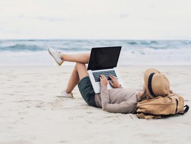 Frau am Strand mit Notebook