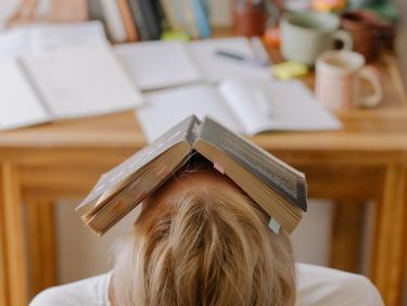 Studentische Verzweiflung: Studierende mit Buch über dem Gesicht wie ein Hausdach
